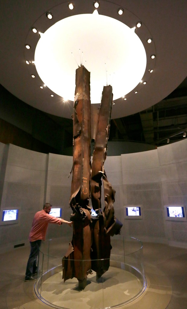In this Sept. 11, 2015 file photo, Landon Cole reaches out to touch steel beams from the World Trade Center on display at the The George W. Bush Presidential Library and Museum in Dallas.