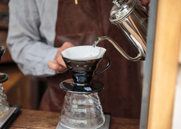 A barista prepares drip coffee.