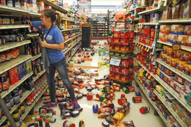 Store employee Talia Pershall, 16, places bottles of syrup back on a shelf while cleaning up at White's Foodliner grocery store in Pawnee, Okla., on Saturday, Sept. 3, 2016, following a 5.6 magnitude morning earthquake in north-central Oklahoma. The tremblor in the edge of the state's key energy-producing areas rattled the Midwest from Nebraska to North Texas.