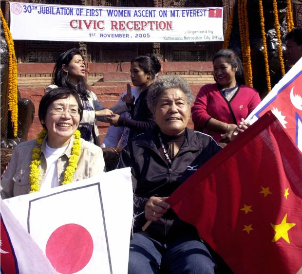 "Two legendary women Everest summiters, Japanese Junko Tabei (L) and Chinese Pang Duo (R) display their national flags at a civic reception on the occasion of the 30th celebration of ''The First Woman's Summit on Mount Everest"" in Kathmandu, November 1, 2005."