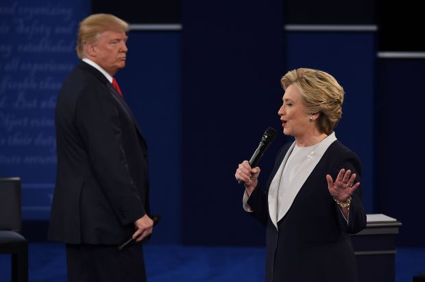 Democratic presidential candidate Hillary Clinton speaks as Republican presidential candidate Donald Trump listens during the second presidential debate at Washington University in St. Louis, Mo., on October 9, 2016.