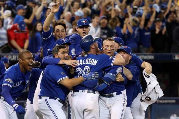 Josh Donaldson #20 of the Toronto Blue Jays celebrates with teammates after the Toronto Blue Jays defeated the Texas Rangers 7-6 in ten innings during game three of the American League Division Series at Rogers Centre on October 9, 2016 in Toronto, Canada.