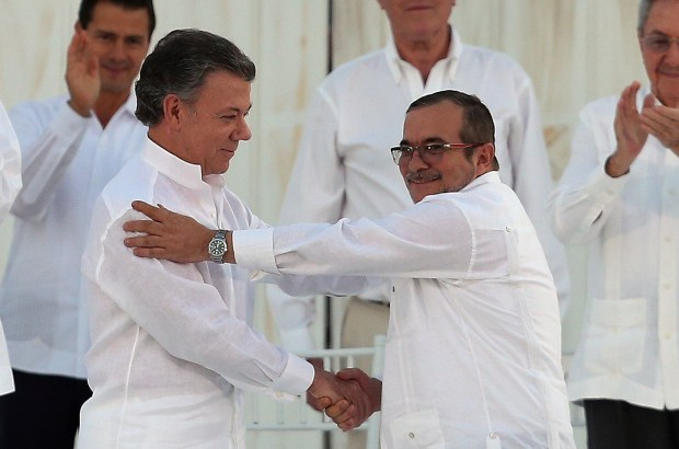 FILE - In this Monday, Sept. 26, 2016 file photo, Colombia's President Juan Manuel Santos, left, and the top commander of the Revolutionary Armed Forces of Colombia (FARC) Rodrigo Londono, known by the alias Timochenko, shake hands after signing a peace agreement between Colombia's government and the FARC to end over 50 years of conflict in Cartagena, Colombia. Santos won the Nobel Peace Prize Friday, Oct. 7, for his efforts to end a civil war that killed more than 200,000 Colombians. (AP Photo/Fernando Vergara, File)