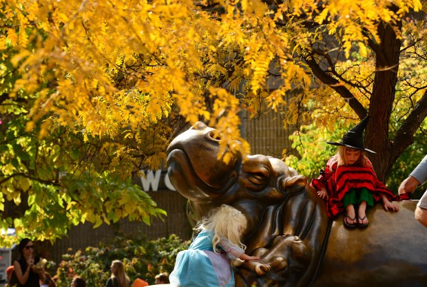 Sammi Billman, 7, dressed as a witch, right and her sister Bella, 4, dressed as Elsa from Frozen, left, climb up on a bronze statue of a mother hippo with her babies at the 30th annual Boo at the Zoo Halloween event at the Denver Zoo in Denver, CO on October 26, 2014.