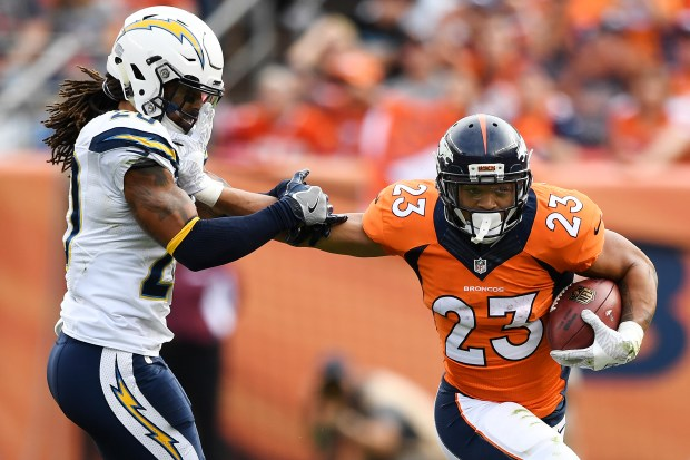 Devontae Booker (23) of the Denver Broncos stiff arms Dwight Lowery (20) of the San Diego Chargers during the second quarter on Sunday, October 30, 2016. The Denver Broncos hosted the San Diego Chargers.