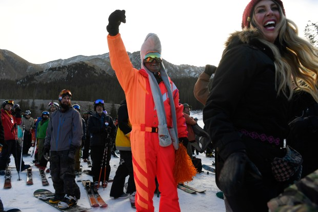 Darren Droge, center, and Gretchen Pleshaw, right, sing and dance while waiting to board the Black Mountain Express lift on opening day at Arapahoe Basin ski area October 21, 2016.