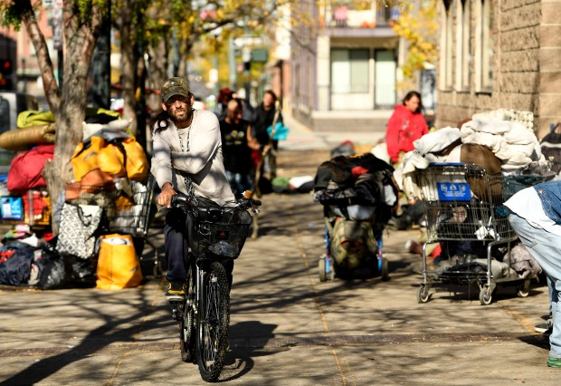 Homeless people line the sidewalks along Park Ave West near the Denver Rescue Mission on October 26, 2016 in Denver, Colorado. After the city performed sweeps to clean up the streets and move the homeless people many have returned to the area with no place else to go.