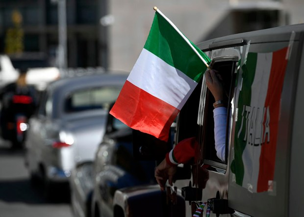 Italian flags wave during Denver's Columbus Day parade on Saturday.