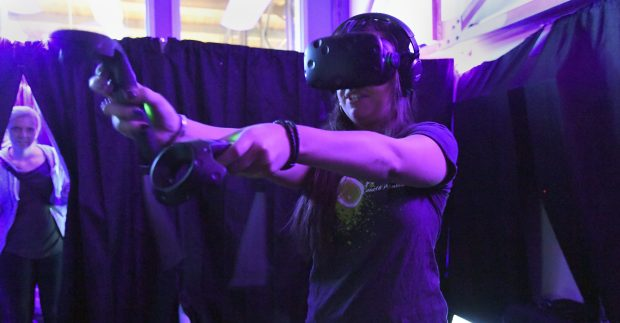 Julianna Hood, 24,  takes her turn at shooting zombies Oct. 20, 2016 at Denver's very own virtual-reality haunted house. The VR tour takes scary inside people's brain using technology to trick the mind into thinking cartoons are scary.