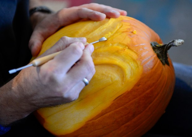 Aaron Dietzen uses a clay sculpting tool to begin to cut a face into a pumpkin, Monday, Oct. 21, 2013, in his studio at his home in Longmont.