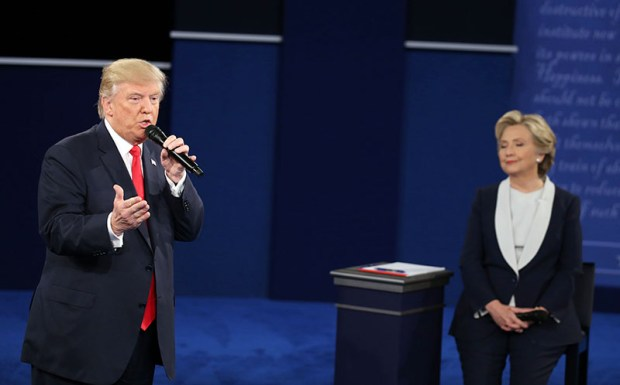 Republican presidential nominee Donald Trump speaks while Democrat Hillary Clinton listens during Sunday night's debate in St. Louis.