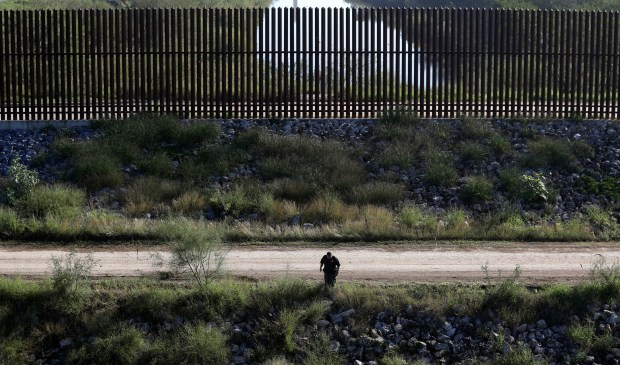 In this Wednesday, Nov. 16, 2016, photo, a U.S. Customs and Border Patrol agent searches for suspected illegal immigrants passing through the area in Hidalgo, Texas. The idea of a concrete wall spanning the entire 1,954-mile southwest frontier collides head-on with multiple realities, like a looping Rio Grande, fierce local resistance, and cost.