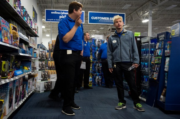 Assistant Store Manager Stephen McCarty directs employees acting as guests through the check out line as they simulate Black Friday during an early morning meeting about Black Friday at Best Buy in Aurora, Colorado on November 19, 2016. Every year Best Buy's employees attend a Black Friday test run that includes a run down of what to expect on the busiest shopping day of the year as well as practicing handling the influx of customers.
