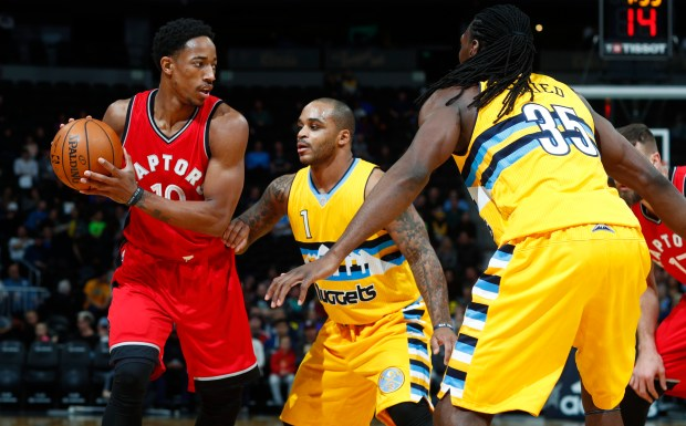 Toronto Raptors guard DeMar DeRozan, left, looks to pass the ball