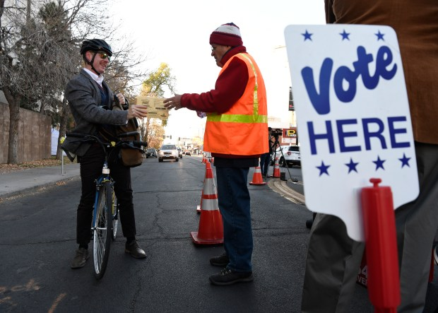 Ryan McCann, left, pulls up on his bicycle to hand over his ballot to Denver Election judge Tim Drago, right, on Election Day at the Denver Elections Division headquarters at Bannock and 14th Avenue in Denver on Nov. 8, 2016.