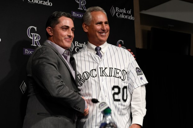 Newly appointed Colorado Rockies manager Bud Black, right, puts on a Colorado Rockies shirt while posing for photographs with Rockies General Manager Jeff Bridich, left,