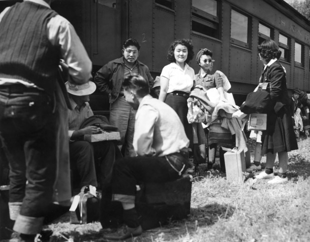 August 30, 1942 - Japanese evacuees stand or sit with their suitcases and belongings in front of a Santa Fe and Topeka passenger train car. The men and women wait for the bus ride to Camp Amache, Granada Relocation Center, southeastern Colorado. (Tom Parker, photographer)