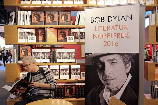 A man reads a book about Bob Dylan at the 2016 Frankfurt Book Fair on Oct. 19 in Frankfurt am Main, Germany. Dylan won this year's Nobel Prize for Literature but did not attend the Nobel ceremony Saturday in Stockholm, Sweden.
