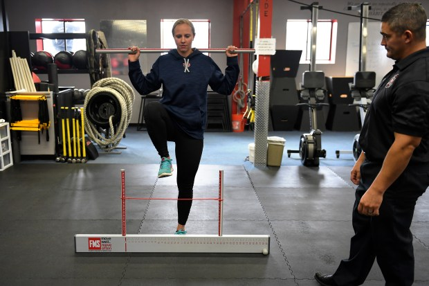 Jackie Fehr, Denver Fire Department fire fighter and peer fitness trainer doing a hurdle step watched by director of the physical therapy department Casey Stoneberger during a functional movement screen at the Rocky Mountain Fire Academy.