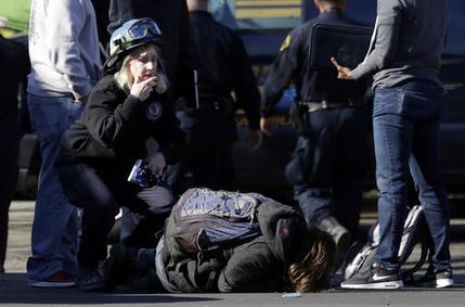 A unidentified man falls to the ground after speaking to authorities outside of a warehouse destroyed by a fire, Dec. 3, 2016, in Oakland, Calif.