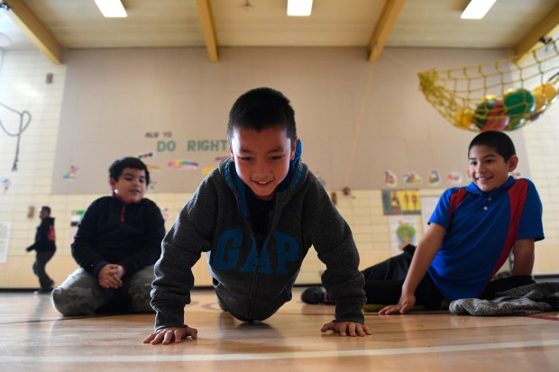 Miguel Rosales, 8, middle, does as many push ups as he can while friends David Perez, 8, left, and Julio Rivera, 9, right, watch during PE class taught by Chris Strater at Lyn Knoll Elementary School on Dec. 14, 2016 in Aurora.