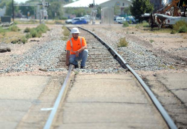 This September 2016 file photo shows William Herbert crouching along the tracks while testing the railroad crossing on 7th Street between Ash Street and Birch Street in Windsor.