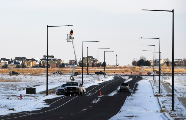 Electricians from Guarantee Electric work on upgrading an LED street lamp by adding a photo controller to it, integrating the lights to a smart system at Panasonic headquarters near Denver International Airport on Dec. 7, 2016.