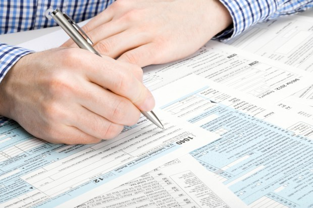 US Tax Form 1040 - man performing tax calculations