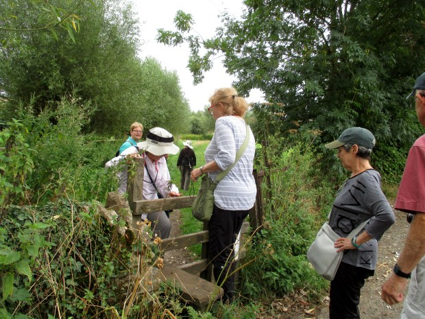 A Classic Journeys walking tour group in Swinbrook, England, climbs one of many stiles (fences) along a walking path through pastures.