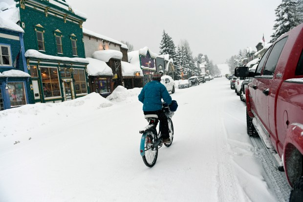 A cyclist makes her way by quaint stores are covered with snow on January 11, 2017 in Crested Butte, Colorado. Downtown Crested Butte has been inundated with more than 100 inches of snow in the past days. More snow is expected in the upcoming days. Helen H. Richardson, The Denver Post