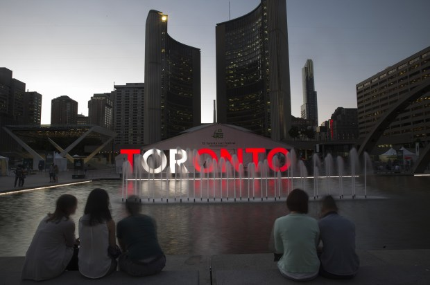 "People sit near an illuminated ""Toronto"" sign stands at Nathan Phillips Square in Toronto, Ontario, Canada, on June 29, 2016."