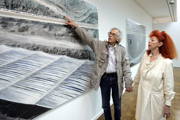 "Artists Christo and Jean-Claude stand beside a drawing of their planned ""Over the River"" project on July 15, 2005."