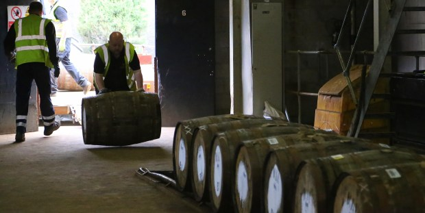 A worker rolls in a barrel of whisky at The Macallan distillery in Craigellachie, Scotland. The distillery, famous for its single malt whisky, offers a detailed tour explaining what goes into making the product.