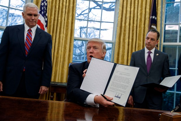President Donald Trump shows off an executive order to withdraw the U.S. from the 12-nation Trans-Pacific Partnership on Monday, as Vice President Mike Pence and White House Chief of Staff Reince Priebus look on.
