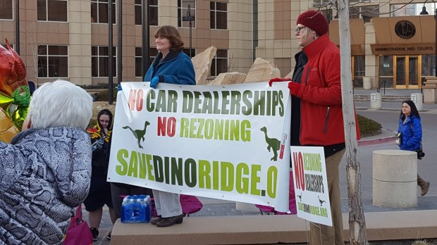 Protestors against the plan to rezone space near Dinosaur Ridge hold a sign outside the Jefferson County Government Building in Golden on Jan. 17, 2017.