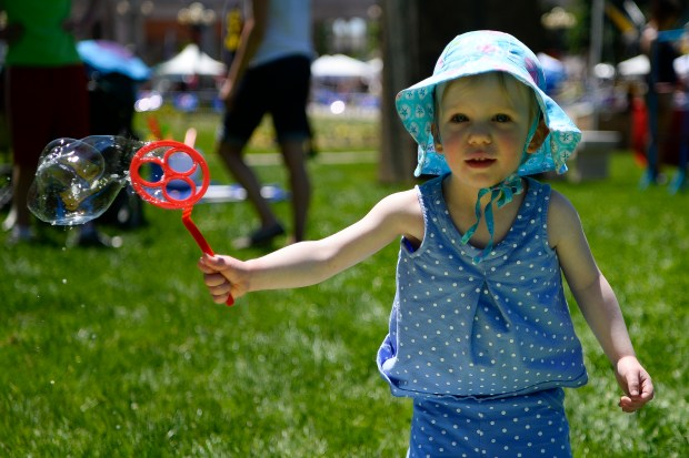 Anna Kaiser makes a bubble during the 45th annual People's Fair at Civic Center Park on June 4, 2016.