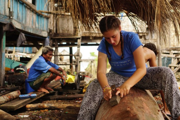 Students hand-carve a dugout canoe in Indonesia as part of a Where There Be Dragon gap-year program.