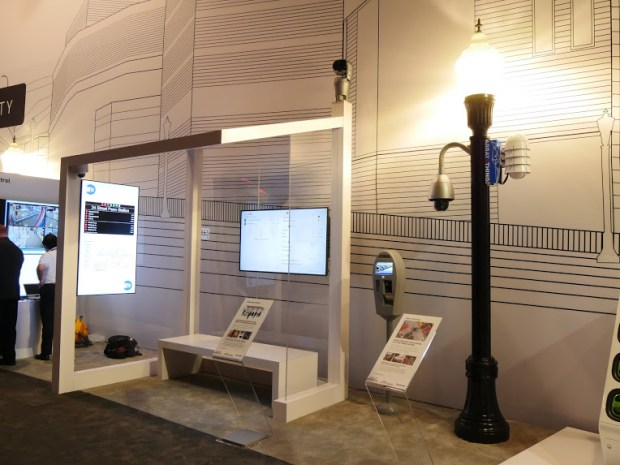 A mock up of a smart transit shelter includes security cameras and interactive video displays.