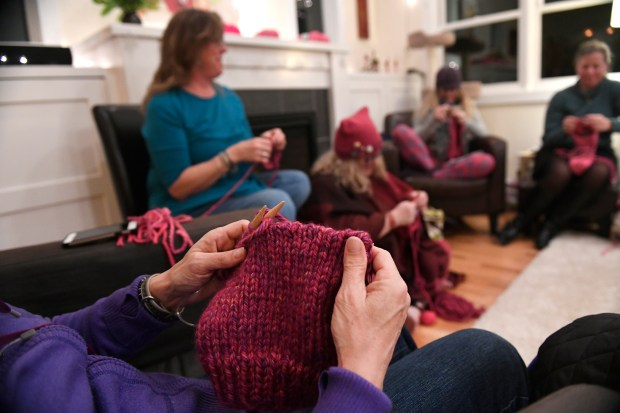Ann Mitchell, just hands shown, puts the finishing touches on a pussyhat as, from left to right in the back Jen Grant, Julie Piller and Debbie Asmus help to knit dozens of pink hats at the home of Jen Grant on Jan. 15, 2017 in Lafayette.