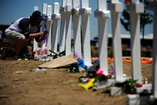 A man writes on a cross at a memorial for the victims of the Aurora Theater Shooting at the intersection of Sable Boulevard and Centerpoint Drive on Sunday, July 22, 2012.