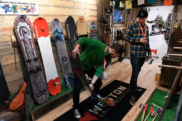 Jason Yap, middle, tests the flexibility of a new snowboard made by local snowboard company Weston Snowboards inside the company's tiny house at the SIA Snow Show at the Colorado Convention Center on Jan. 29, 2017 in Denver.