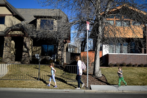 A woman and her children walk between sections of sidewalk and non-sidewalk walkways in south Denver.