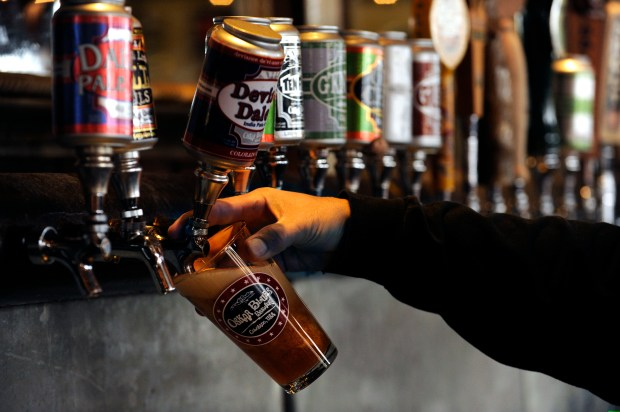Bartender Lucas Green fills a glass of beer at Oskar Blues restaurant in Longmont in 2011.