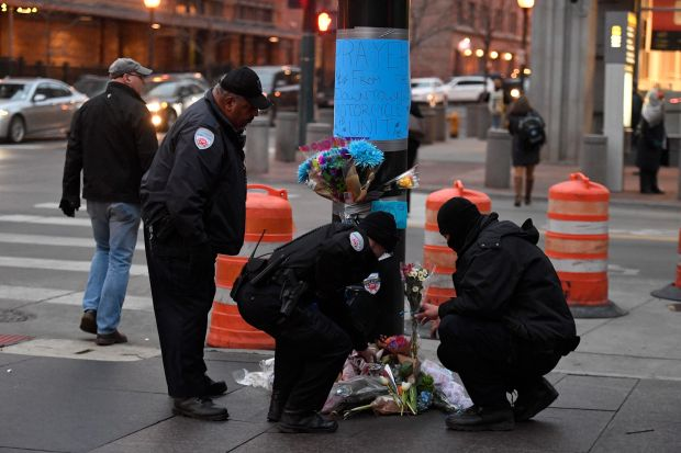 Security officers fix some flowers that have fallen over at a memorial on 16th and Wynkoop, Feb. 1, 2017, where a security officer was killed identified as Scott Von Lanken, 56, of Loveland.