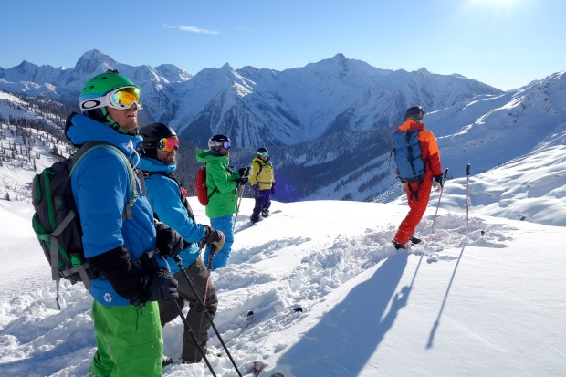 Part of a group takes a breather while watching others take a heliskiing run in British Columbia.
