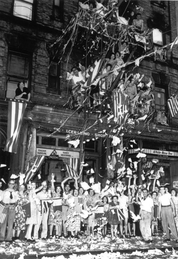 August 14, 1945: A jubilant crowd of American Italians are seen as they wave flags and toss papers in the air while celebrating Japan's unconditional surrender in their neighborhood in New York City.