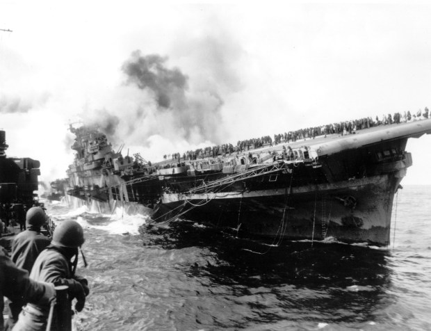 March 19, 1945: The USS Santa Fe lies alongside the heavily listing USS Franklin to provide assistance after the aircraft carrier had been hit and set afire by a single Japanese dive bomber, during the Okinawa invasion off the coast of Honshu, Japan.