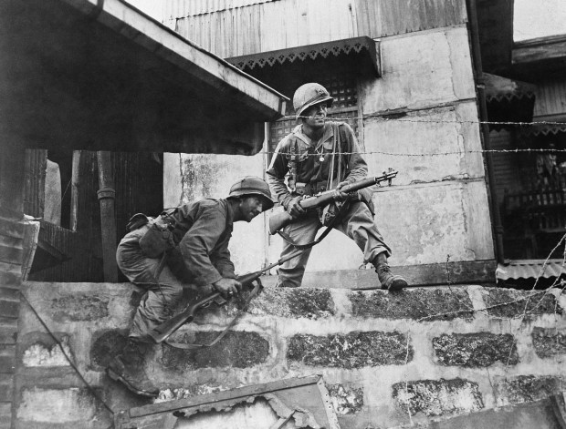 Feb. 13, 1945: Two Yank Infantrymen of the hard fighting 37th American division, climb through some Japanese barbed wire during street fighting in Manila in the Philippines.