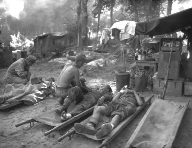November 12, 1944: U.S. medics are seen as they treat wounded comrades at an portable surgical unit during the 36th Division's drive on Pinwe, Burma.