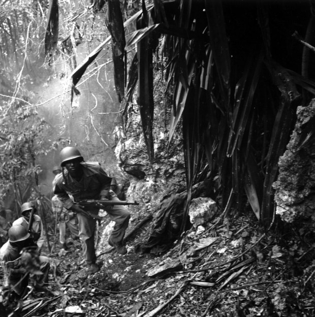 March 10, 1945: U.S. troops in the Pacific islands continued to find enemy holdouts long after the main Japanese forces had either surrendered or disappeared. Guam was considered cleared by August 12, 1944, but parts of the island were still dangerous half a year later. Here, patrolling Marines pass a dead Japanese sniper. These Marines may belong to the Fifty-second Defense Battalion, one of two black units sent to the Pacific.